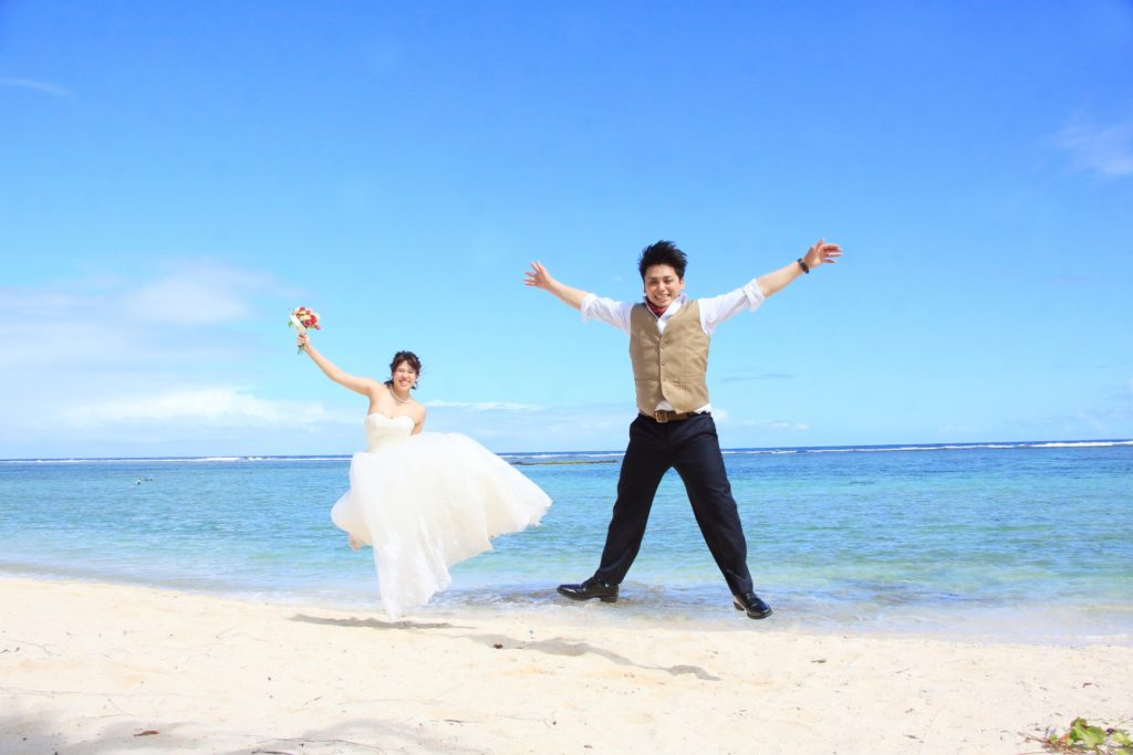 結婚した新郎新婦が海でジャンプ