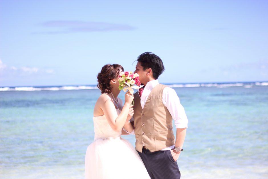 結婚して海でキスをする新郎新婦