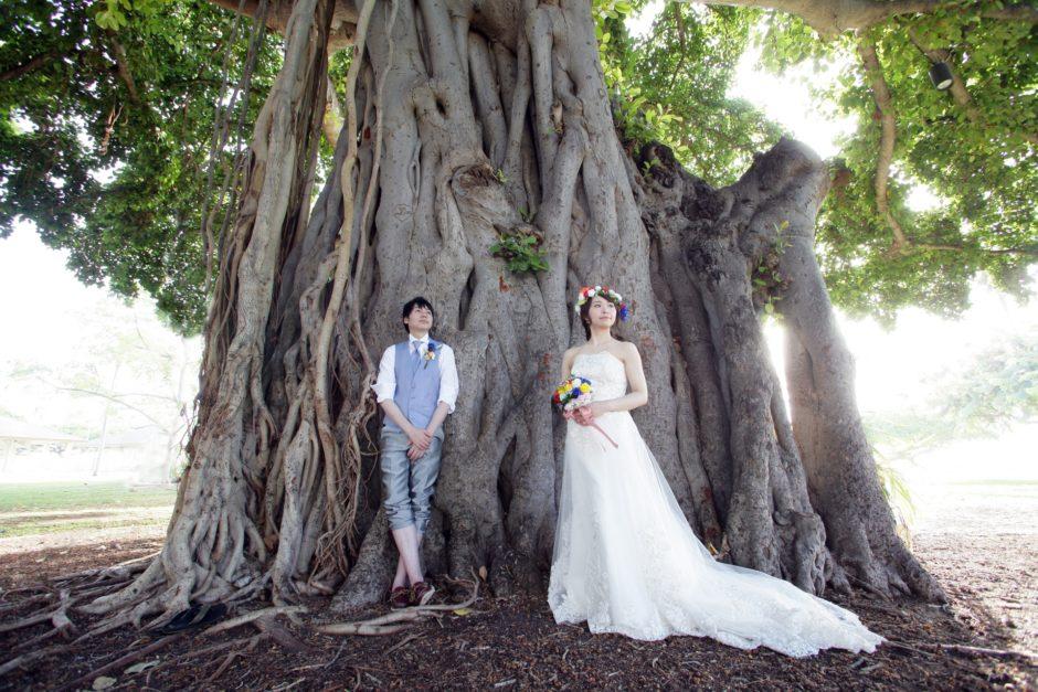 結婚式で木にもたれ掛かる新郎新婦