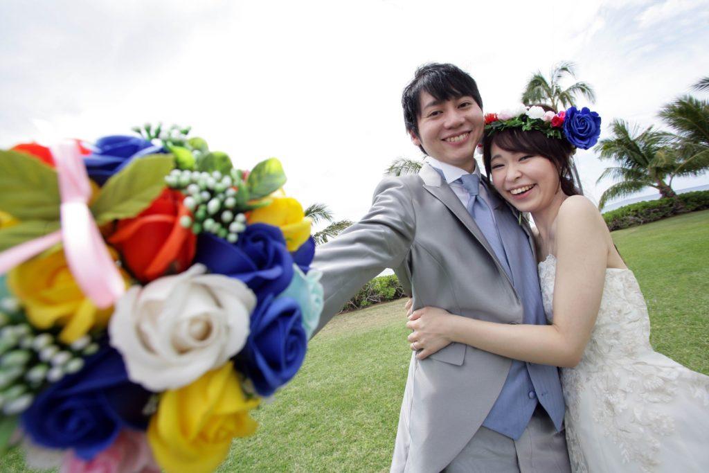 婚活ブログ_結婚式で花束をかざす新郎新婦