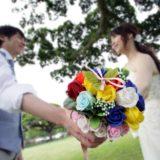 リゾートウェディングで花束を持って見つめ合う新郎新婦