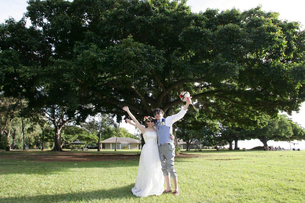 木の前で手を挙げる新郎新婦