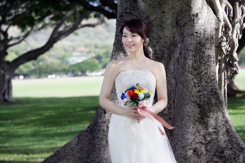 木の前で花束を持ってほほ笑む新婦